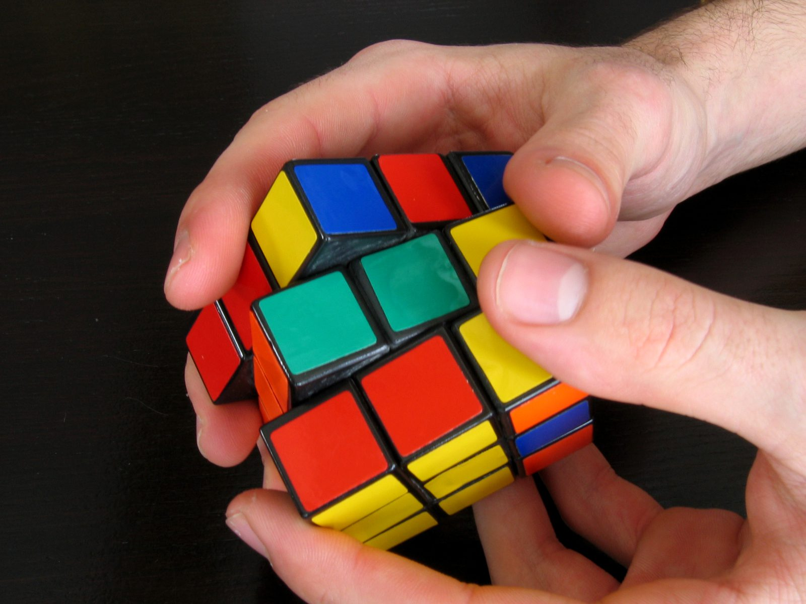 Hands working on a Rubik's cube